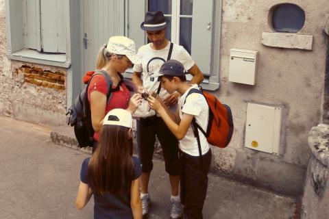 Deux adultes et deux enfants se concertent pour résoudre la chasse au trésor.