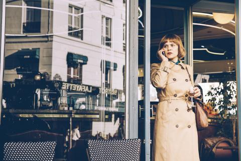 Une femme en imperméable passe un coup de fi sur la porte d'un café, un verre à la main.