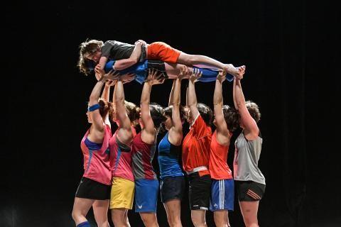 Une femme est portée à l'horizontale par sept autres femmes à bout de bras.