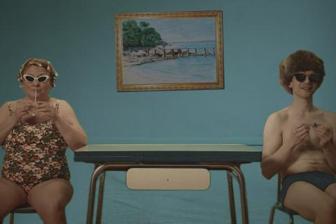 Photo de deux personnages, assis en maillot de bain et lunettes de soleil, de part et d'autre d'une table de cuisine.