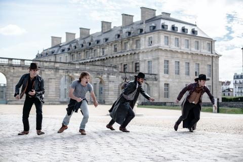 Photo des quatre personnages commençant à courir, avec un château en arrière-plan.