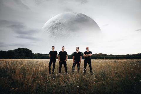 Portrait du groupe dans un champ avec une énorme Lune en arrière-plan.
