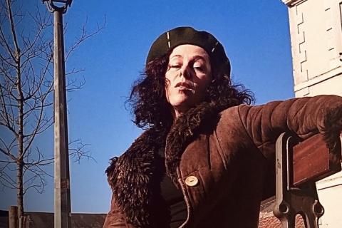 Portrait de la personne incarnant Barbara sur un banc public, sous un réverbère.