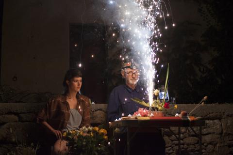Deux personnes devant une table d'où jaillit une colonne d'étincelles.