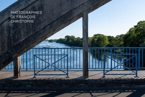 La Loire photographiée depuis un pont. L'image est barrée par la structure en béton du pont, et les rambardes en métal.