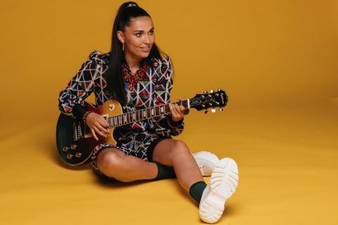 Camille Esteban, souriante, jouant de la guitare par terre.