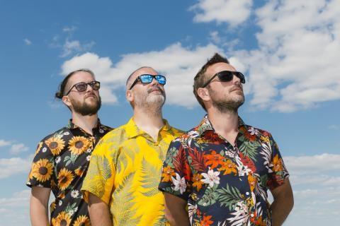 Portrait du groupe portant des lunettes de soleil, leurs têtes toutes levées dans la même direction, vers le haut droit du cadre
