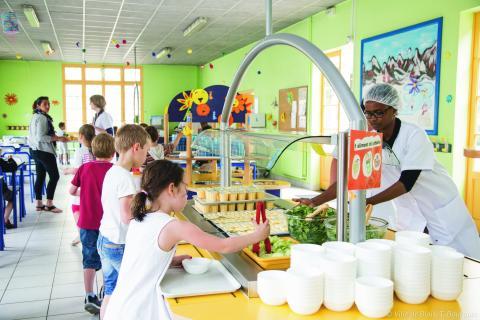 Des enfants se servent à manger dans une cantine.