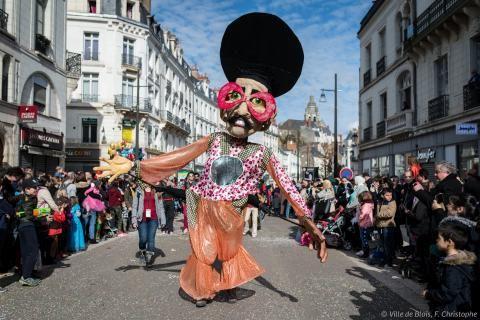 Figure géante défilant au milieu de la foule pour le carnaval.