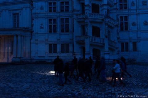 Visite nocturne du Château royal : un guide mène le groupe dans la cour intérieure à l'aide d'une lampe torche.