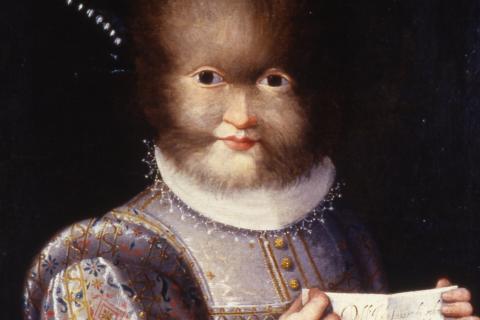 Portrait d'Antonietta Gonzaleds, au visage velu et souriant, tenant sa lettre manuscrite racontant succinctement son histoire.