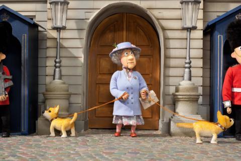 La reine d'Angleterre se promène avec les chiens, dont l'un renifle un garde.