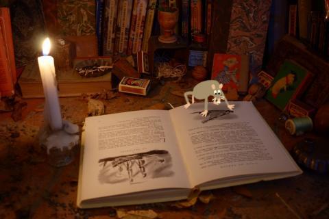 Une souris lit un livre à la lumière d'une bougie.