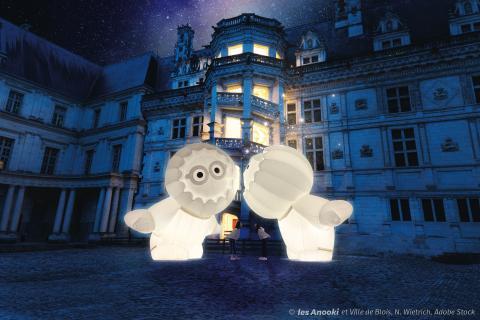De nuit, les Anooki (deux inuits géants rayonnants) se font la bise devant l'escalier du Château royal illuminé de l'intérieur, sous les étoiles. Deux personnes sous les Anooki miment leur bise.