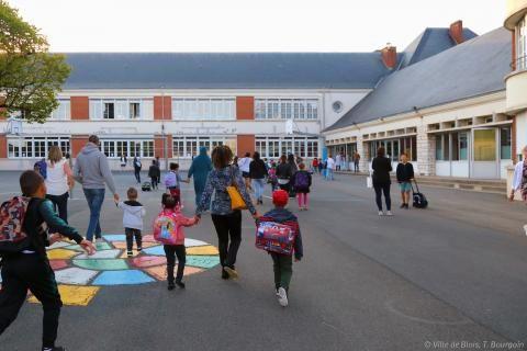 Des enfants sont accompagnés par leurs parents dans la cour d'une école.