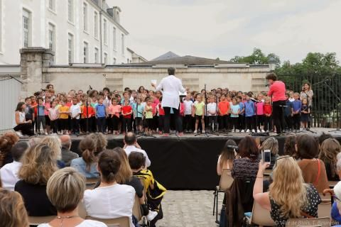 La chorale de l'école du Foix chante sur scène, devant le public.