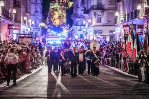 L'harmonie municipale défile au milieu de la rue Denis-Papin, avec la foule sur les trottoirs et la Joconde sur l'escalier Denis-Papin en arrière-plan.