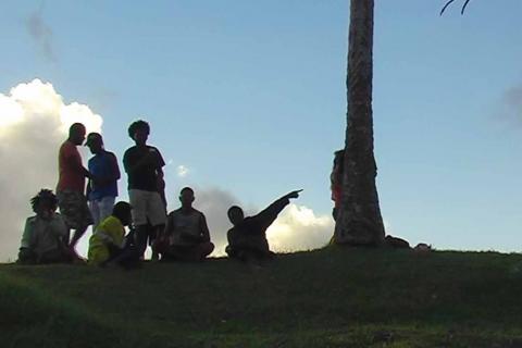 Un groupe d'hommes sont en contre-jour au sommet d'une colline, les nuages en arrière-plan.