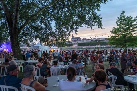 La foule est attablée pour dîner et discuter en bord de Loire, dans le port de la Creusille, pendant qu'un concert a lieu en arrière-plan.