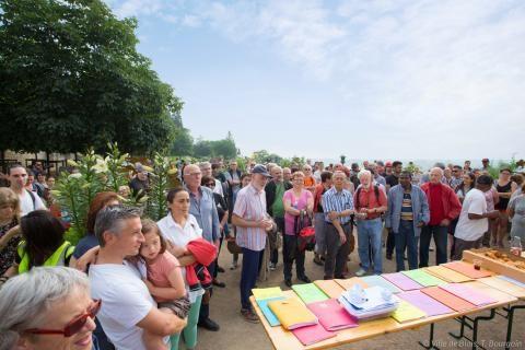 Une foule de personnes est réunie dans les jardins de l'évêché autour d'une table présentant les différents ateliers.