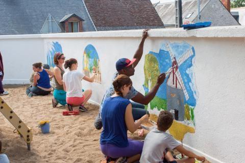 Des adultes et des enfants peignent une fresque sur le mur d'une aire de jeux extérieure.