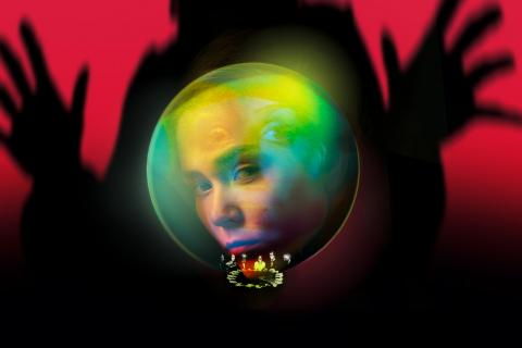 Un visage est enfermé dans une boule de cristal. Une silhouette semble s'en emparer en arrière-plan. Détail : on distingue dans la boule de cristal des personnes attablées autour d'une table se tenant la main.