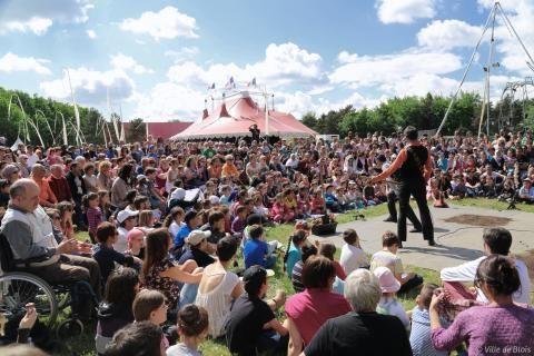 Un groupe d'artistes se produit en plein air devant une foule accroupie autour d'eux.
