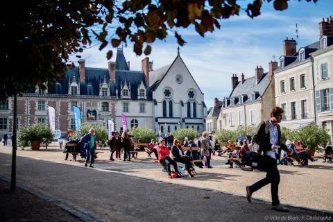 Nombreuses personnes assises sur les bancs de la place du Château.