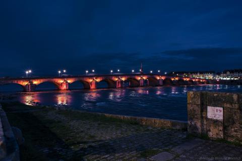 Le pont Jacques-Gabriel depuis la rive gauche, mis en lumière avec une teinte orangée et des projecteurs pointant vers le haut, respectant la biodiversité.