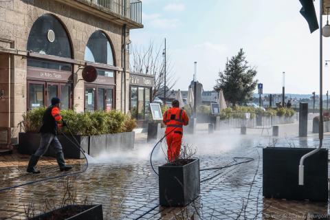 Deux agents équipés de lances à eau haute pression nettoient la rue Henri-Drussy, en direction du pont.