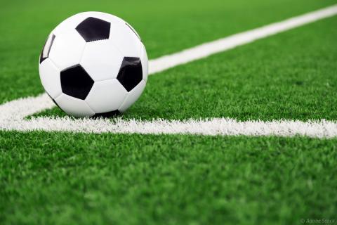 Balon de football posé sur une pelouse, dans l'angle d'un marquage au sol.