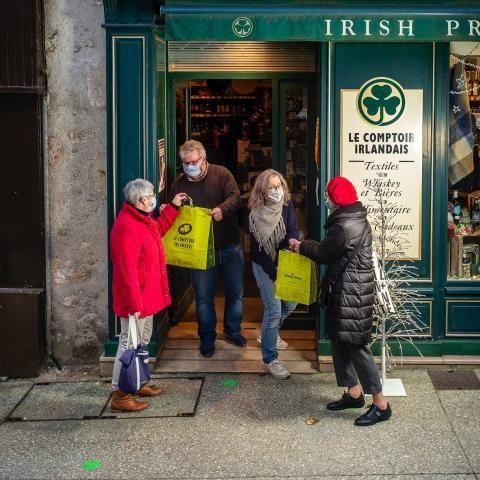 Commerçants remettant leur commande à deux clientes sur le pas de leur commerce. Tout le monde est masqué.