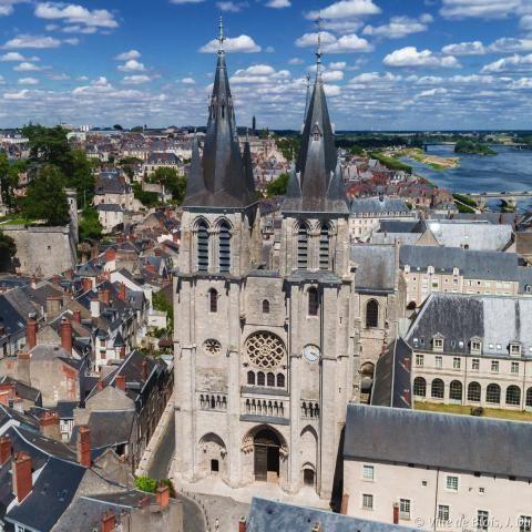 La façade de l'église Saint-Nicolas vue du ciel, avec le Château royal, la Loire et le pont Jacques-Gabriel en arrière-plan.