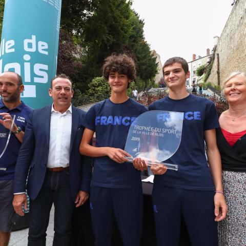 L'entraîneur, le maire et l'adjointe aux Sports sont aux côtés des lauréats pour la remise de leur trophée.