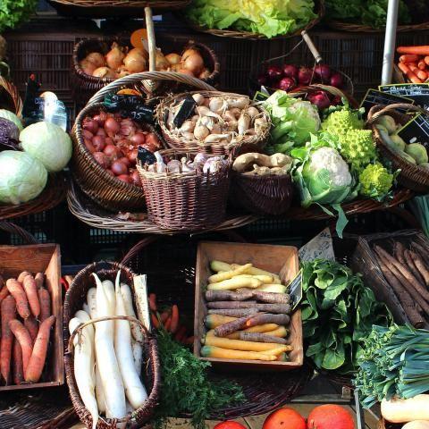 Étal rempli de gros paniers de légumes : carottes, poireaux, oignons, choux, salades, etc.