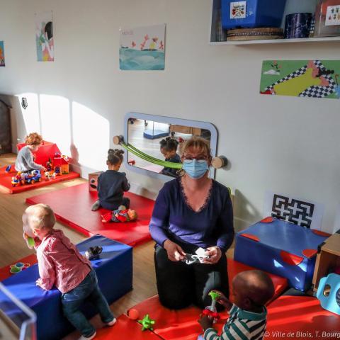 Une assistante maternelle masquée au milieu des enfants dans le Ram Picoty. Chaque enfant joue sur son tapis.