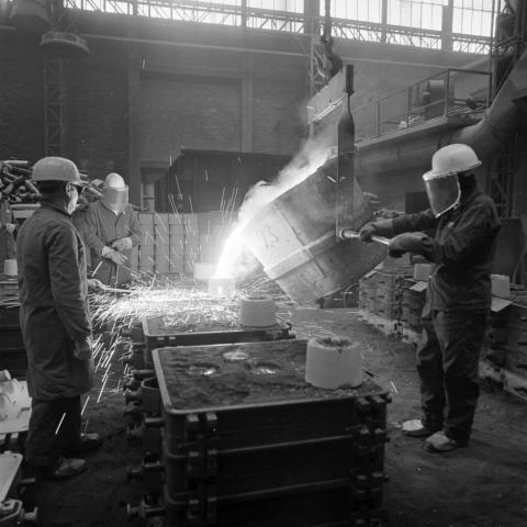 Photo de 1977 d'ouvriers masqués faisant couler de l'acier dans la fonderie de Roanne.