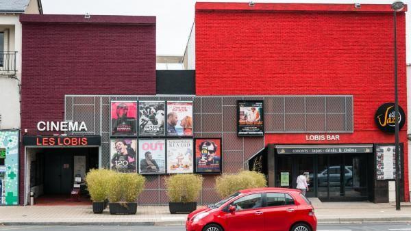 Façade caractéristiquement rouge du cinéma Les Lobis et du bar du même nom, attenant.