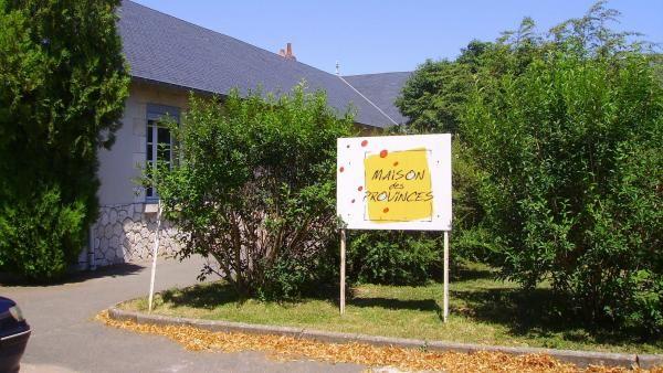 Entrée de la Maison des Provinces, avec de nombreux arbres et de la pelouse.