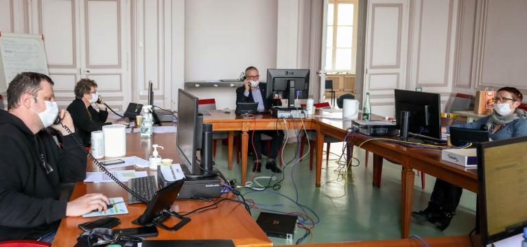 Cinq personnes autour d'une table ronde, équipés de masque, d'ordinateur et éloignées les unes des autres, répondent aux appels de la cellule d'appels, à l'Hôtel de Ville.