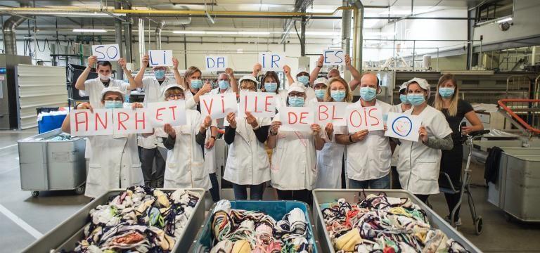 Les équipes de l'ANRH tiennent chacun une lettre pour former la phrase «ANRH et Ville de Blois solidaires», devant une pile de masques.