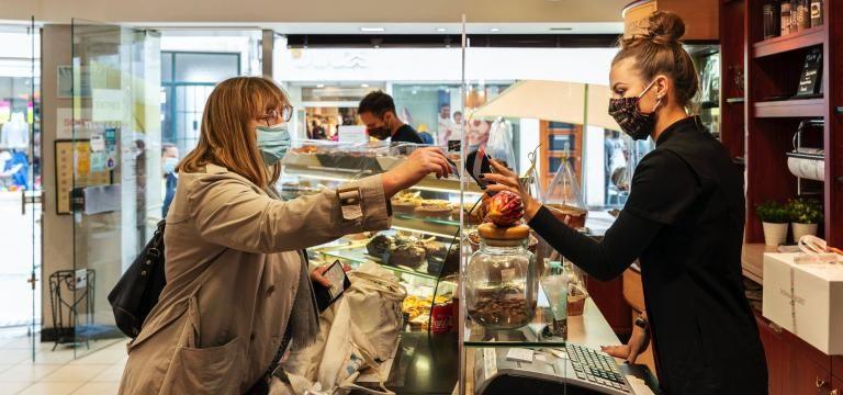Une personne masquée paie son pain à la boulangère masquée également.
