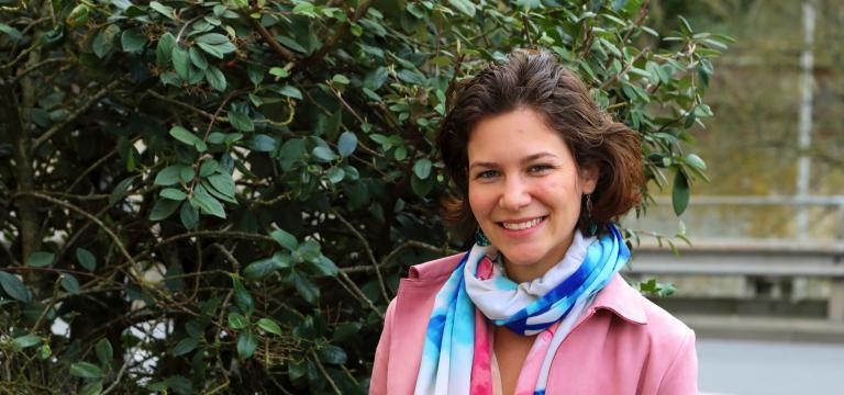 Portrait de Muriel Deparis près d'un arbuste.