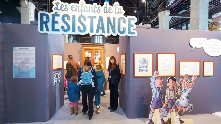 Entrée de l'exposition «Les enfants de la Résistance», avec une agente d'accueil souriante.