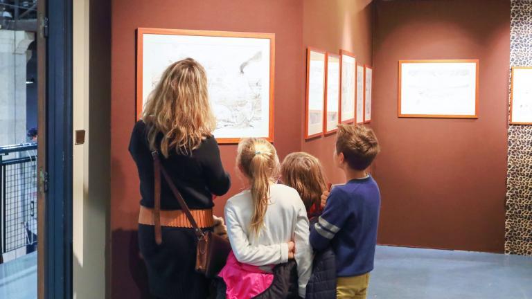 Une femme et trois enfants observent attentivement une planche de bande dessinée.