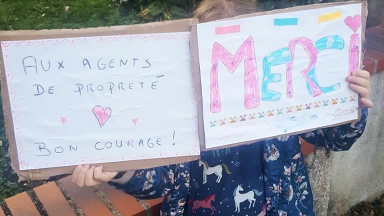 Une petite fille tient un panneau qu'elle a dessiné, disant «merci au personnel de la collecte des déchets et de la propreté».