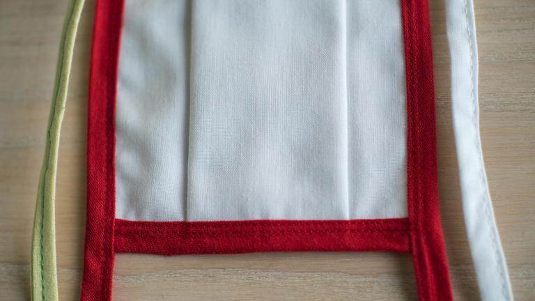 Gros plan sur les coutures d'un masque, mettant en évidence les trois épaisseurs de tissu.