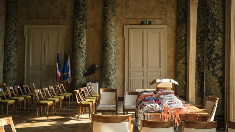 Photo de la table de la salle des mariages de l'Hôtel de Ville, recouverte de centaines de masques.