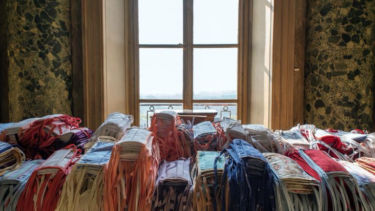 Gros plan sur la table de la salle des mariages de l'Hôtel de Ville, recouverte de centaines de masques.