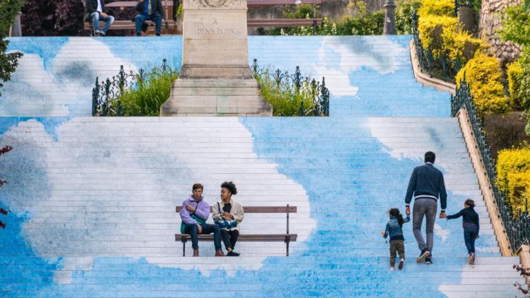 Les contremarches de l'escalier Denis-Papin entièrement recouvertes d'un dessin de ciel bleu et de nuages. Des personnes sont assises sur un banc au milieu et d'autres gravissent les marches, au milieu du ciel.